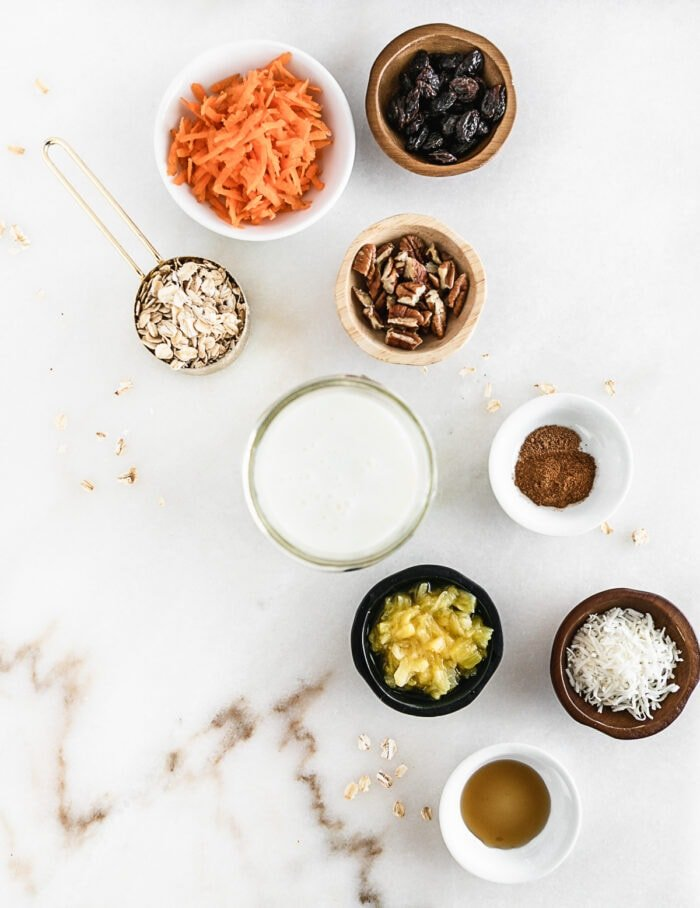 overhead view of ingredients needed to make carrot cake overnight oats on a white background.