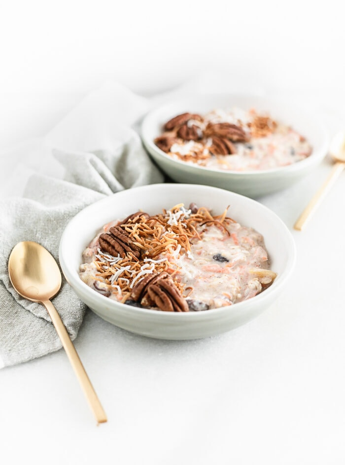 bowl of carrot cake overnight oats topped with toasted pecans and coconut flakes with a gold spoon beside it.