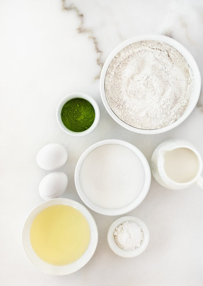 overhead view of ingredients needed to make mini matcha cupcakes on a white background.