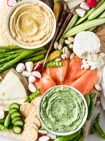 overhead view of a spring snack board with bowls of hummus and green dip, fresh veggies, smoked salmon and cheese.