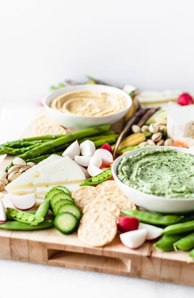 straight on view of spring snack board with hummus, veggies, cheese, and crackers.