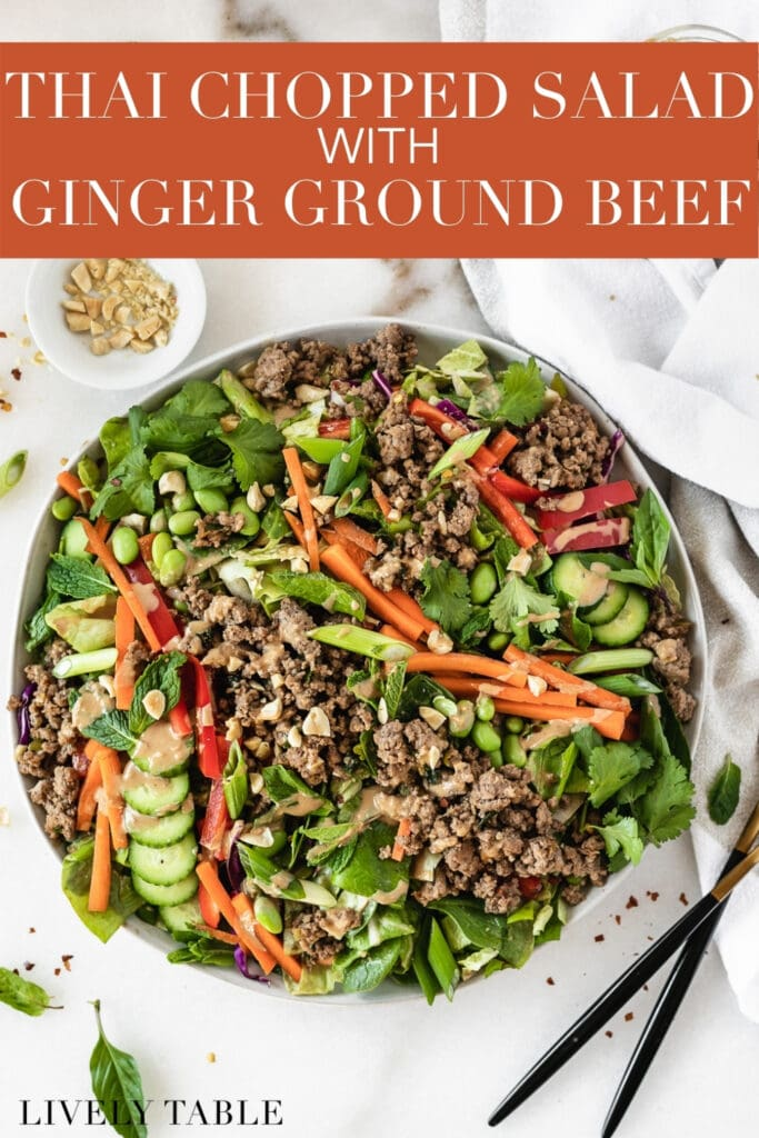 overhead view of thai ginger ground beef salad with a bowl of chopped peanuts and two gold and black forks beside it with text overlay.