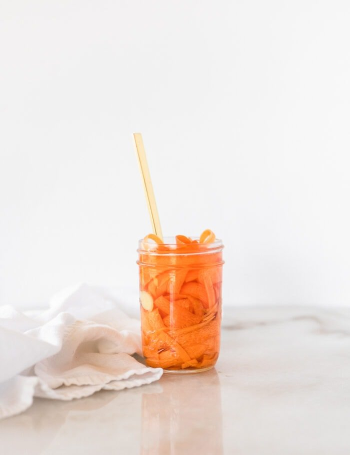 jar of pickled carrots with a gold fork in it and a white napkin beside it.