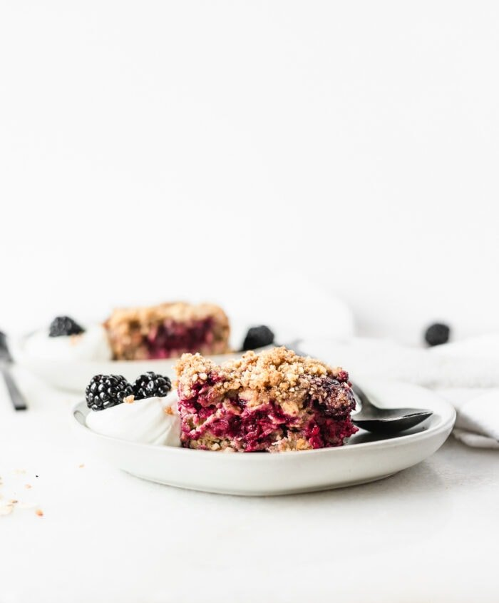 square of blackberry crumble baked oatmeal on a white plate with yogurt and blackberries with a black spoon beside it.