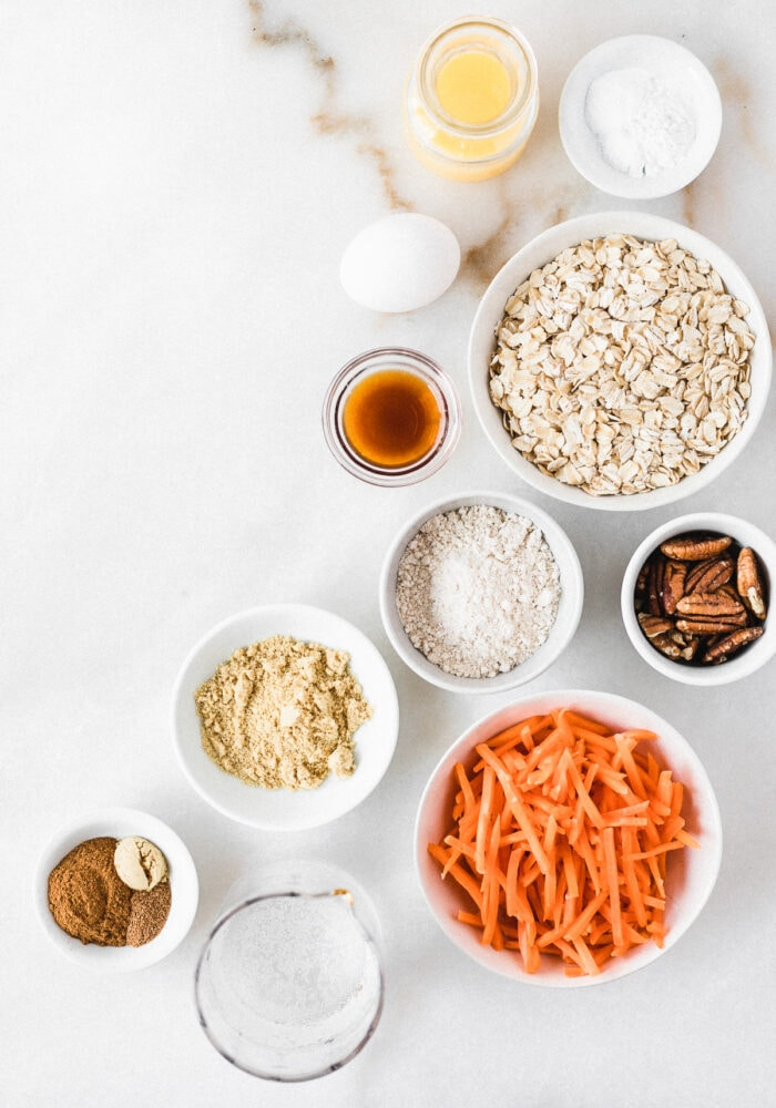 overhead view of ingredients needed for healthy carrot cake pancakes on a white background.