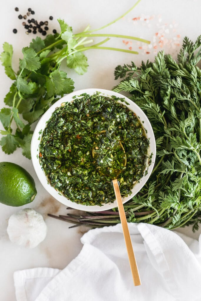overhead view of carrot top chimichurri in a small white bowl with a gold spoon in it surrounded by chimichurri ingredients.