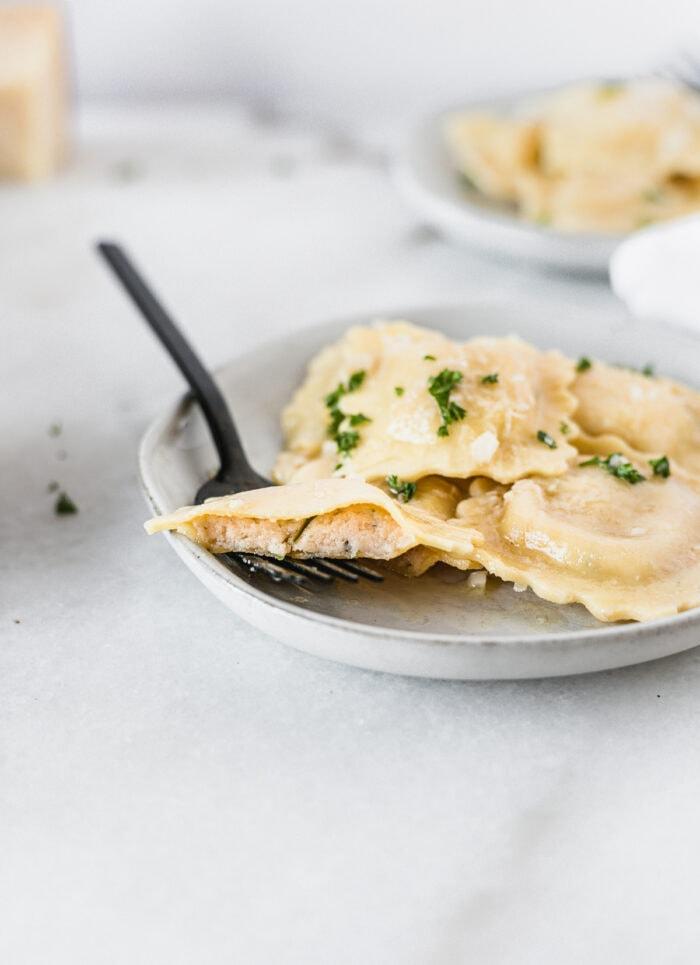 piece of lobster ravioli cut in half on a black fork sitting on a plate of ravioli.