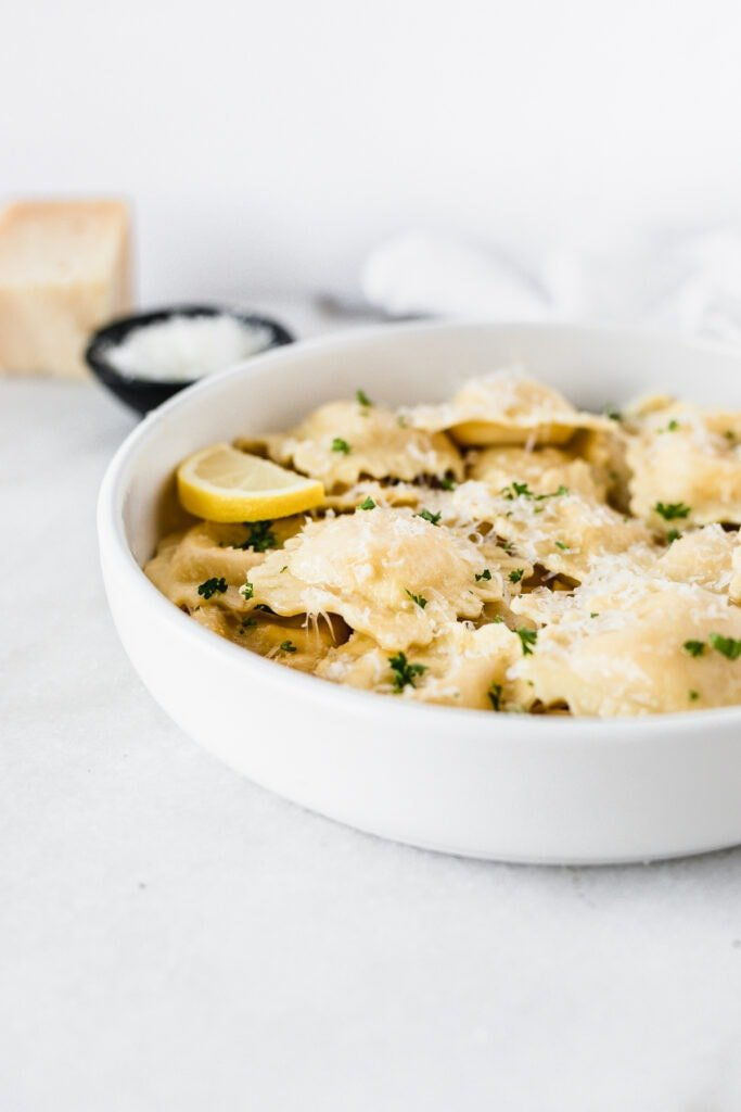 white bowl of lobster ravioli with brown butter sauce topped with parmesan and parsley.