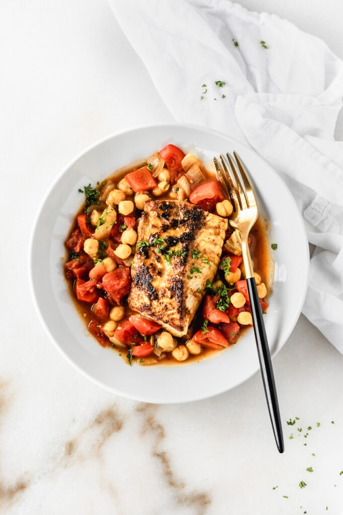 overhead view of moroccan cod with stewed chickpeas and tomatoes in a white bowl with a black and gold fork in it.