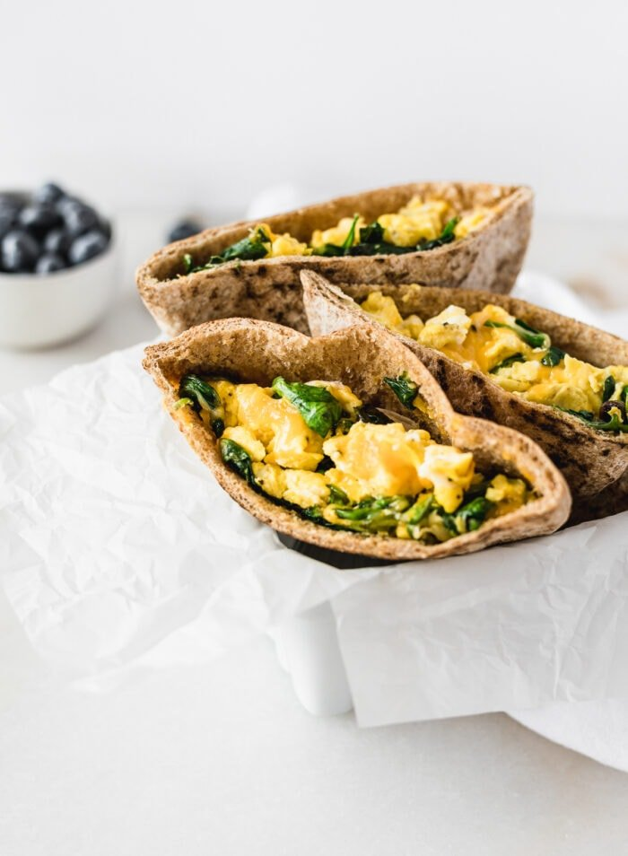 three spinach egg and cheese breakfast pita halves in a white basket with a bowl of blueberries behind it.