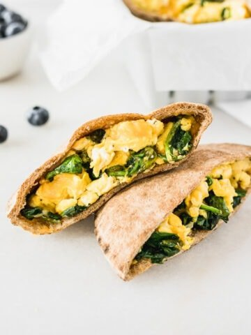 spinach egg and cheese breakfast pita halves stacked on top of each other with a bowl of blueberries in the background.