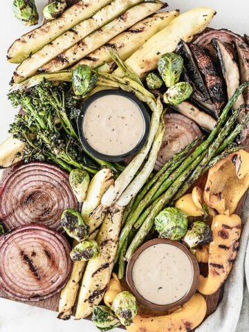 overhead view of various marinated grilled vegetables with small bowls of dipping sauce on a wooden board.