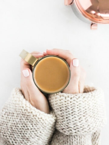 overhead view of hands around a cup of coffee with a copper french press in the corner.