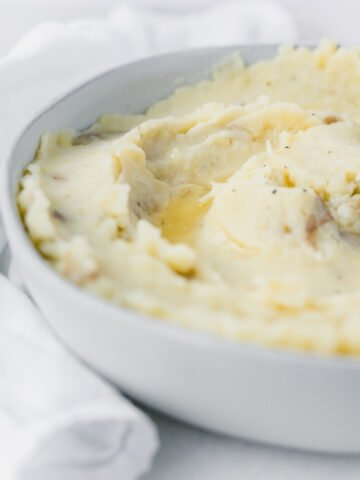 closeup of rustic mashed potatoes in a grey bowl with melted butter on top.