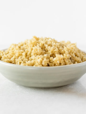 cooked quinoa in a small grey bowl on a white background.