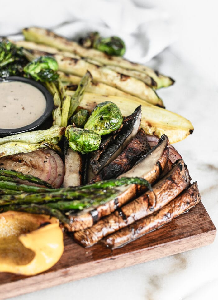 grilled sliced portobello mushrooms and asparagus on a serving board with other grilled vegetables.