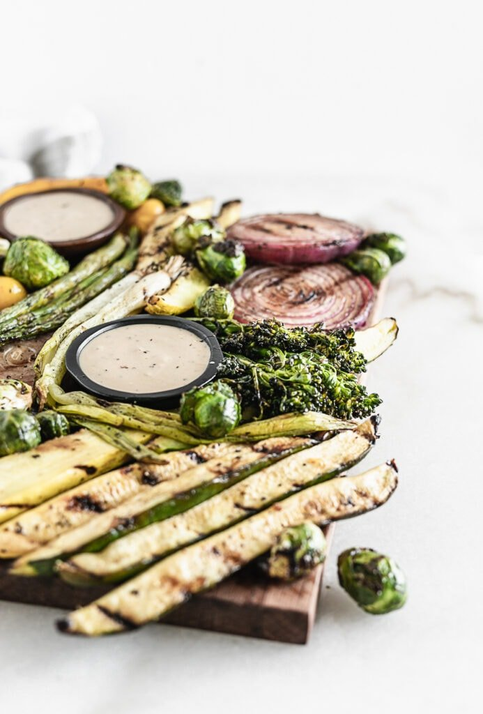 closeup of grilled zucchini spears and brussels sprouts on a serving board with other grilled vegetables and bowls of dipping sauce.