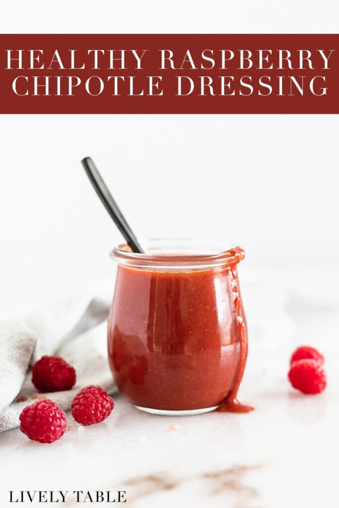 raspberry chipotle dressing in a glass jar with a black spoon in it surrounded by fresh raspberries with text overlay.