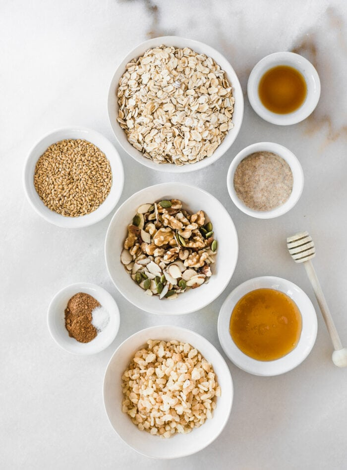 overhead view of ingredients needed to make sourdough discard granola on a white marble background.