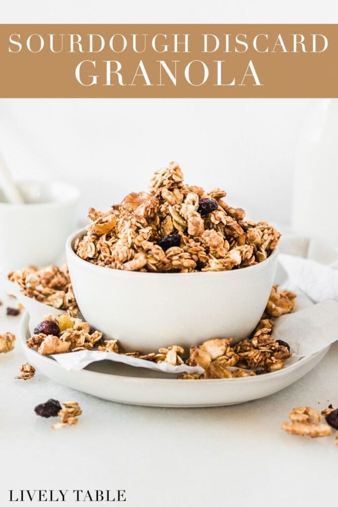 sourdough discard granola in a white bowl on top of a plate with granola clusters all around it with text overlay.