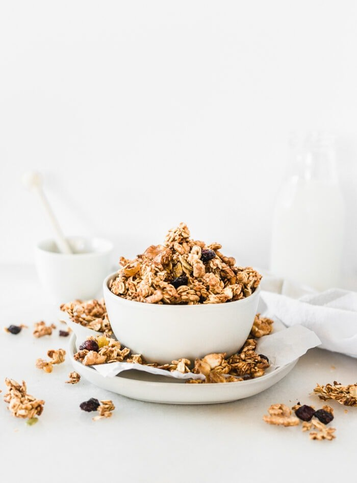 sourdough discard granola in a white bowl on top of a plate with granola clusters all around it.