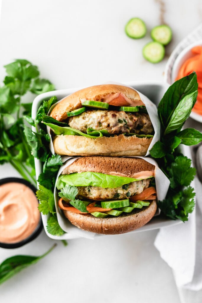 overhead view of two thai chicken and pork burger with avocado, pickled carrots, herbs and lettuce surrounded by fresh herbs and a bowl of sriracha sauce.