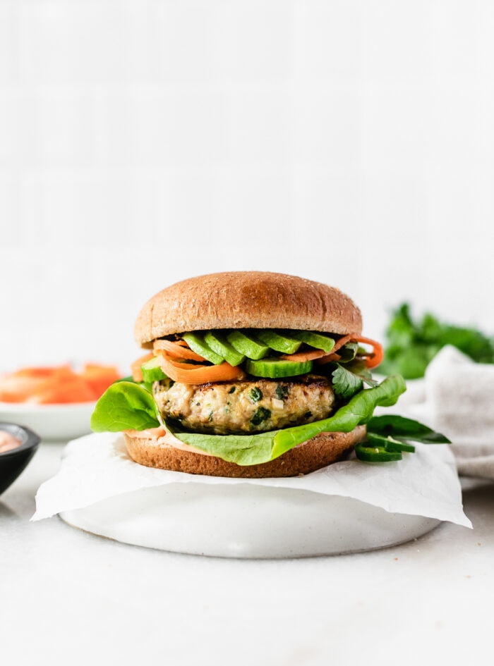 thai chicken and pork burger with avocado, pickled carrots and lettuce on a parchment covered plate.