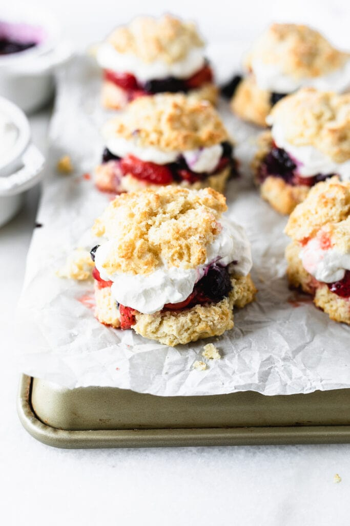 closeup of strawberry and blueberry shortcakes on a parchment lined tray.