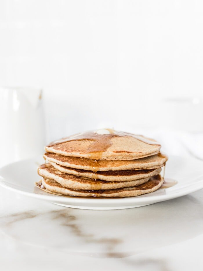stack of sourdough pancakes with butter and syrup on a white plate.