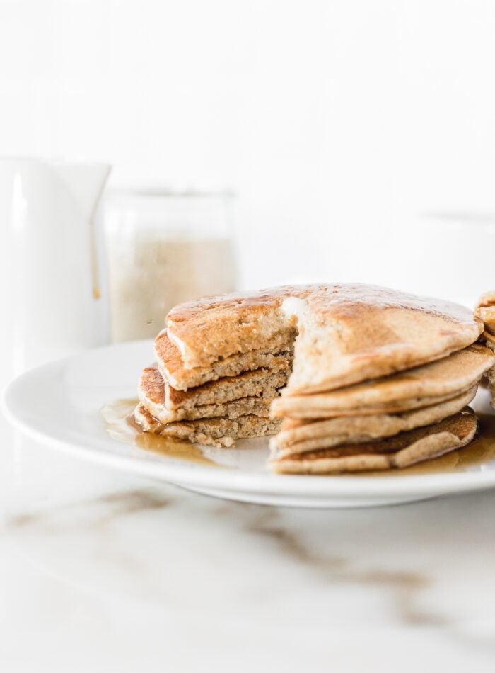 stack of sourdough pancakes on a white plate with a bite cut out.