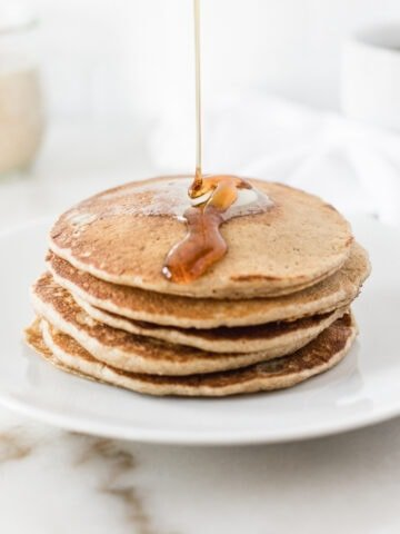 syrup being poured over a stack of sourdough discard pancakes on a white plate.