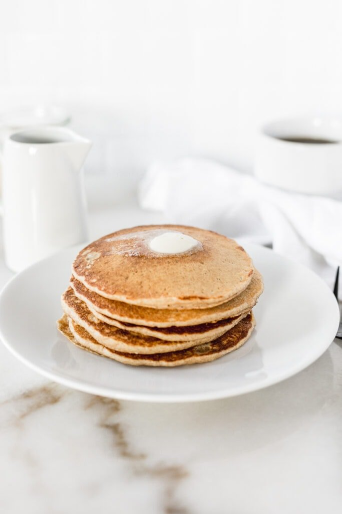 stack of sourdough pancakes with butter on top on a white plate.