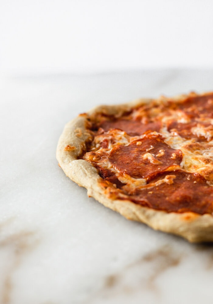 Closeup of sourdough pizza crust on pepperoni pizza on a white marble backdrop.