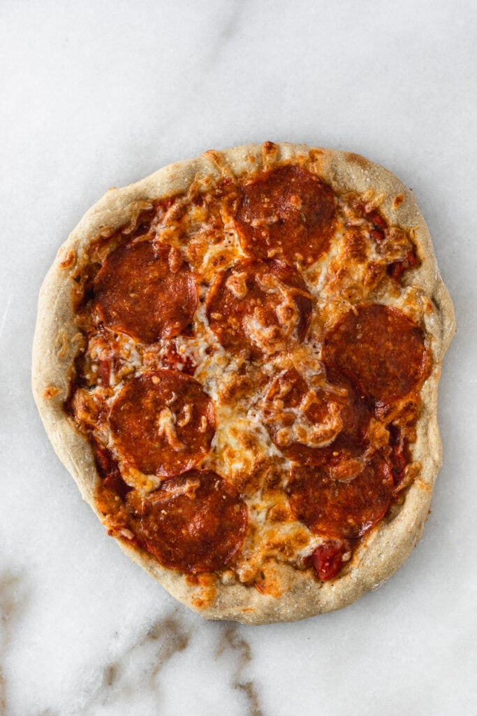 overhead view of pepperoni pizza on a white marble backdrop.