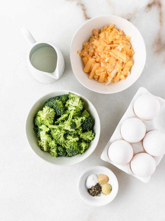 overhead view of ingredients needed to make broccoli cheddar egg muffins on a white marble background.