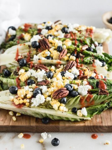 grilled romaine halves topped with corn, goat cheese, blueberries and dressing on a wood cutting board.