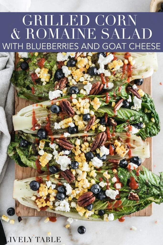 overhead view of grilled romaine halves topped with corn, goat cheese, blueberries and dressing on a wood cutting board with text overlay.