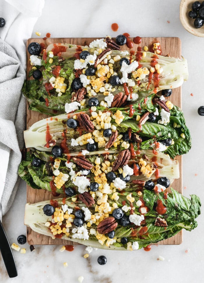 overhead view of grilled romaine halves topped with corn, goat cheese, blueberries and dressing on a wood cutting board.