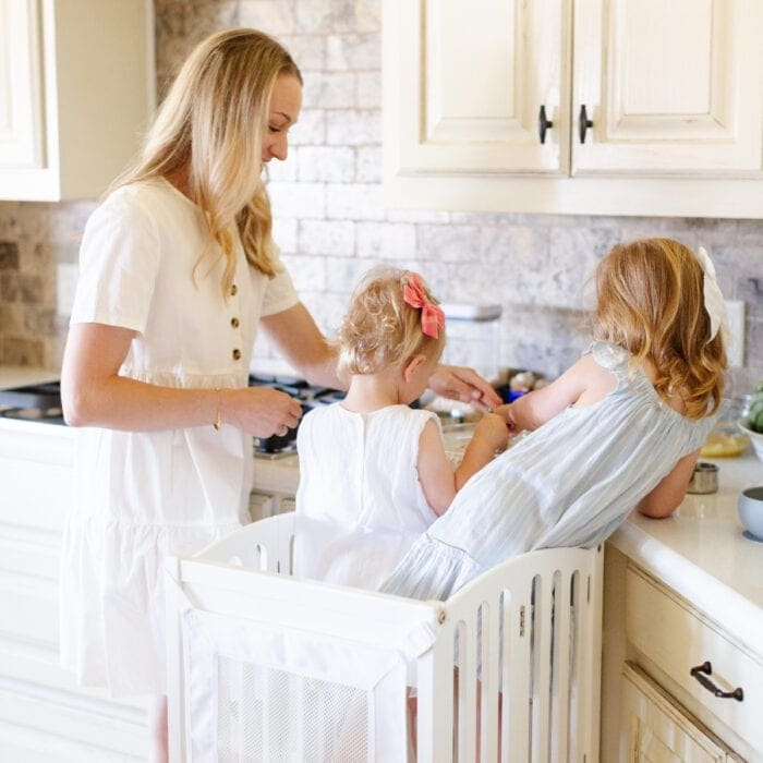 two toddlers standing on a learning tower with a woman in a white dress next to them in the kitchen.