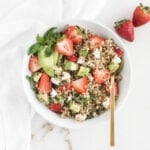 overhead view of strawberry avocado quinoa salad in a white bowl with a gold spoon in it.