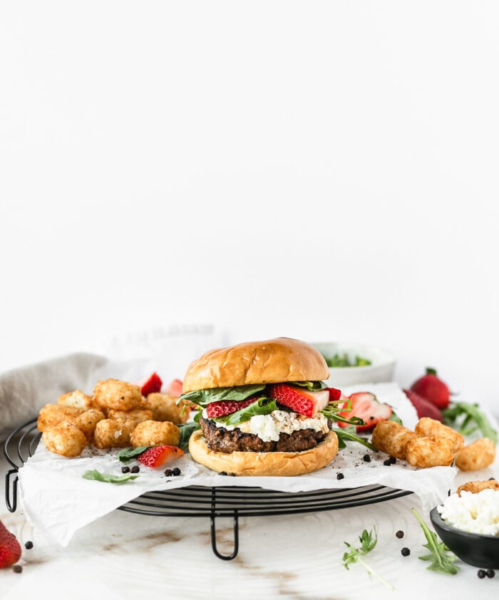 strawberry basil goat cheese burger on a black wire rack topped with parchment with tater tots and strawberries in the background.