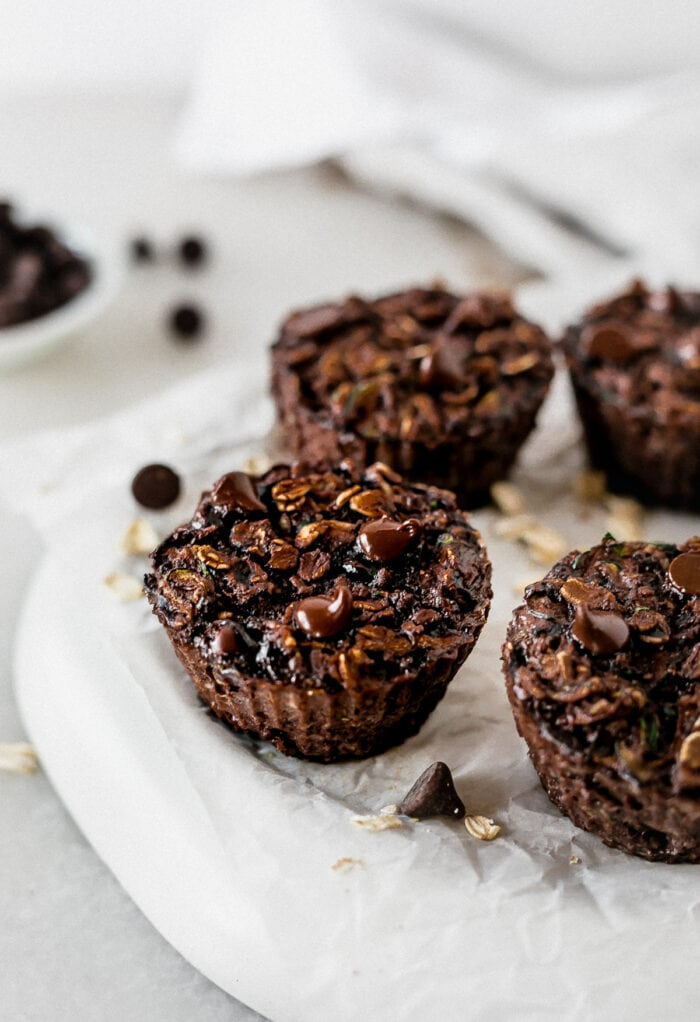 closeup of double chocolate zucchini baked oatmeal cups on a parchment lined plate.
