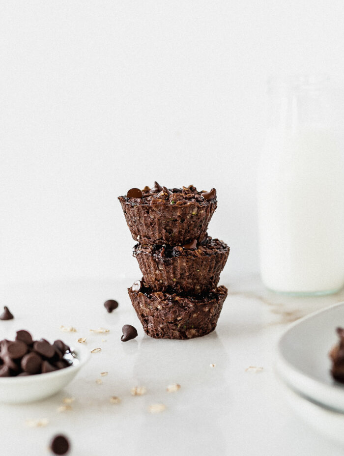 three double chocolate zucchini baked oatmeal cups stacked with a bottle of milk in the background.