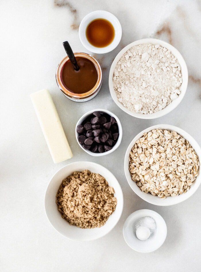 overhead view of ingredients needed to make dream bars on a white marble background.