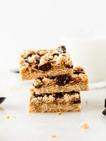 three dream bars stacked with a spoon of caramel next to the and a glass of milk in the background.