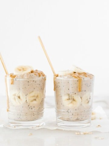 two glasses of peanut butter banana overnight oats with banana slices and peanut butter on top and gold spoons in them.