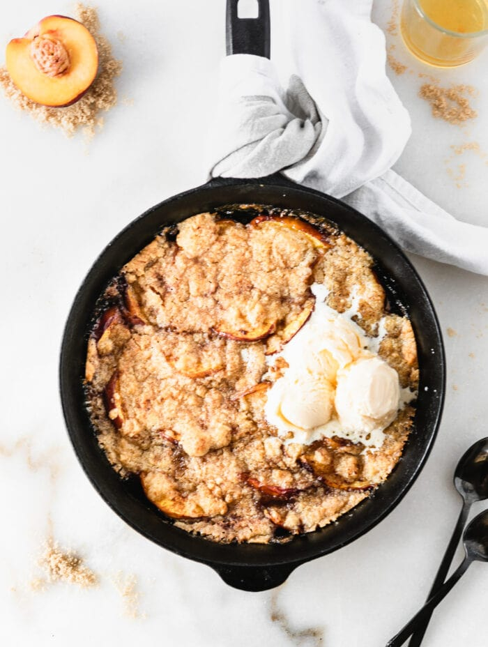 overhead view of smoked bourbon peach cobbler in a cast iron skillet with ice cream on top.