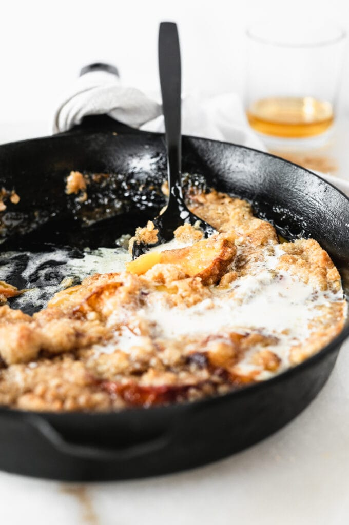 black spoon in a half-eaten skillet of smoked bourbon peach cobbler with melted ice cream on top.
