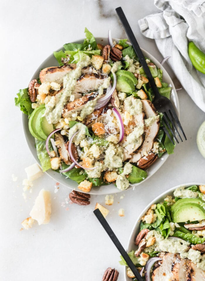 overhead view of southwest green chile chicken caesar salad with a black fork in it.
