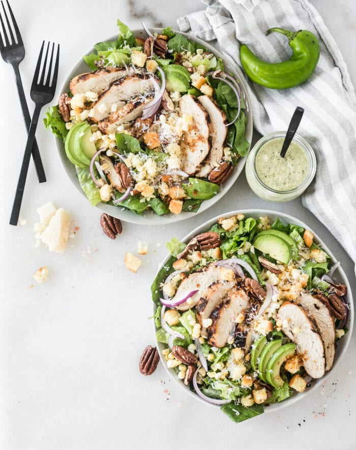 overhead view of two southwest green chile chicken caesar salads with black forks and a jar of green chile dressing beside them.
